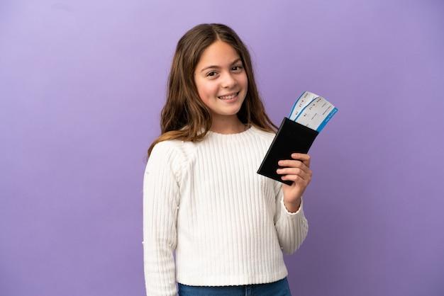 Petite fille caucasienne isolée sur fond violet heureuse en vacances avec passeport et billets d'avion