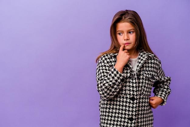 Petite fille caucasienne isolée sur fond violet petite fille caucasienne isolée sur fond violet détendue en pensant à quelque chose en regardant un espace de copie.