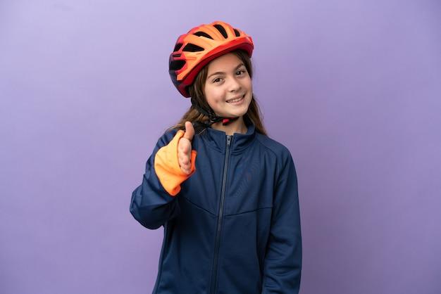Petite fille caucasienne isolée sur fond violet se serrant la main pour conclure une bonne affaire