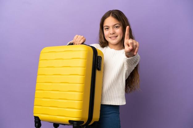 Petite fille caucasienne isolée sur fond violet en vacances avec valise de voyage et en comptant un
