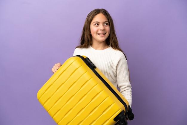 Petite fille caucasienne isolée sur fond violet en vacances avec valise de voyage