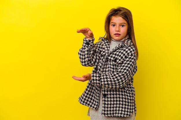 Petite fille caucasienne isolée sur jaune choqué et étonné tenant un espace de copie entre les mains.