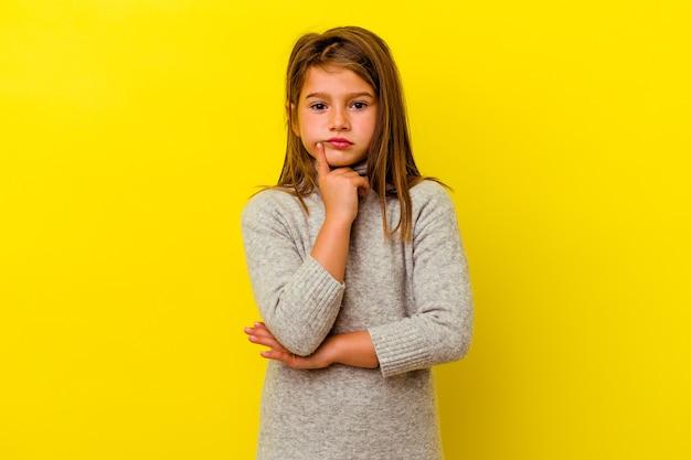Petite fille caucasienne isolée sur jaune en contemplant, en planifiant une stratégie, en réfléchissant à la manière d'une entreprise.