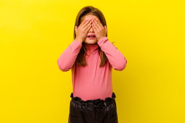 Petite fille caucasienne isolée sur jaune couvre les yeux avec les mains, sourit largement en attente d'une surprise.