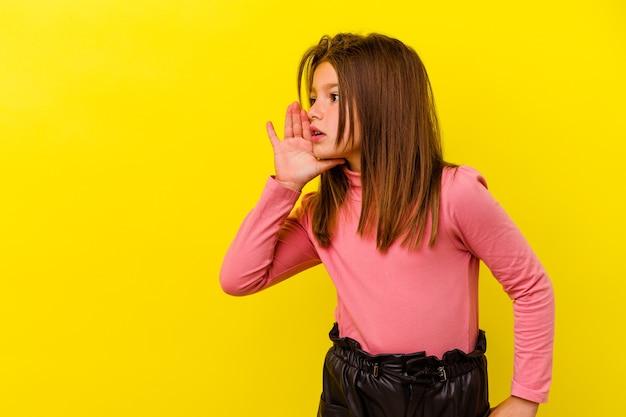Petite fille caucasienne isolée sur jaune dit une nouvelle secrète de freinage à chaud et à la recherche de côté