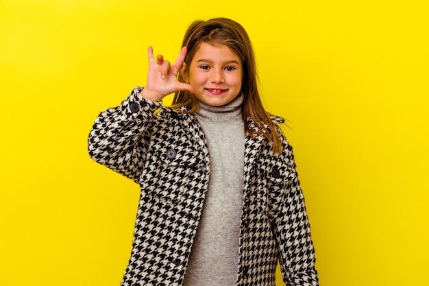 Petite fille caucasienne isolée sur jaune montrant un geste de cornes comme un concept de révolution.
