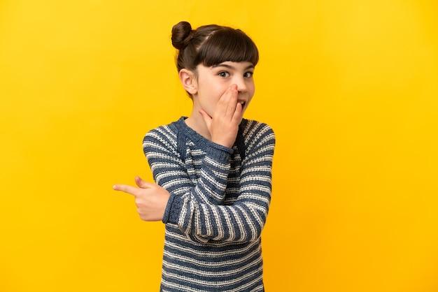 Petite fille caucasienne isolée sur jaune pointant vers le côté pour présenter un produit et chuchoter quelque chose