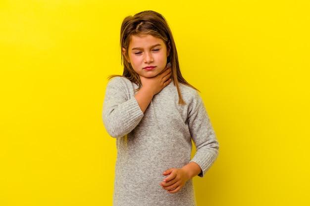 Petite fille caucasienne isolée sur jaune souffre de douleurs dans la gorge en raison d'un virus ou d'une infection.
