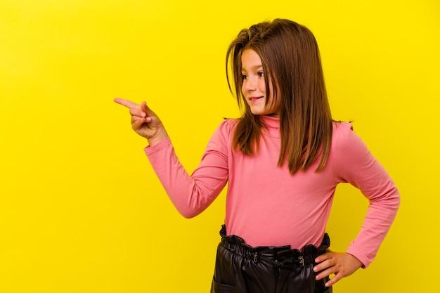 Petite fille caucasienne isolée sur jaune souriant joyeusement pointant avec l'index loin.