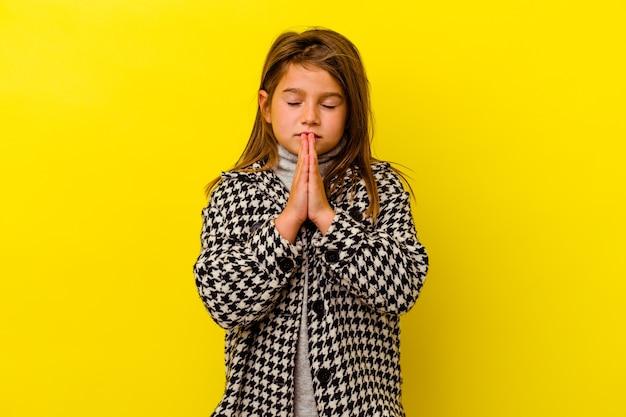 Petite fille caucasienne isolée sur jaune tenant la main en priant près de la bouche, se sent confiante.