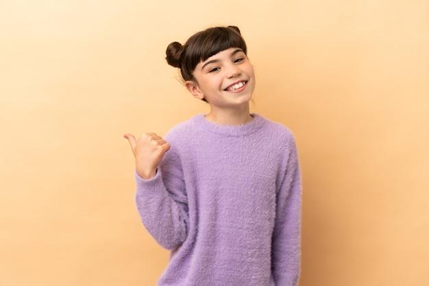 Petite fille caucasienne isolée sur un mur beige pointant vers le côté pour présenter un produit