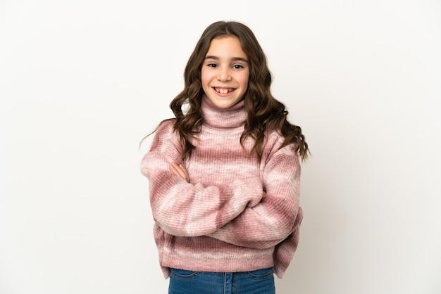 Petite fille caucasienne isolée sur un mur blanc en gardant les bras croisés en position frontale