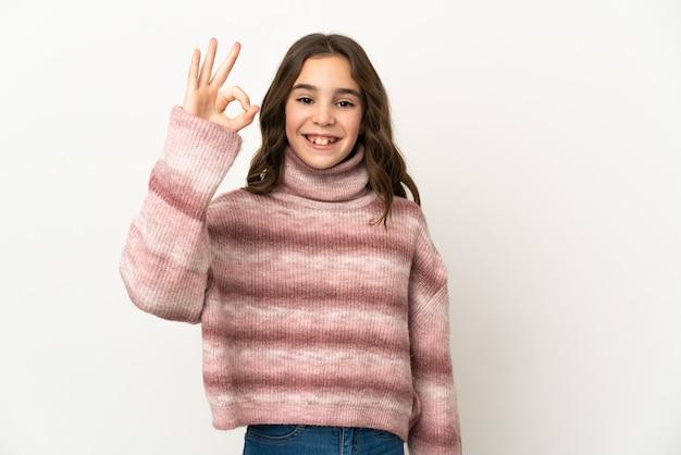 Petite fille caucasienne isolée sur un mur blanc montrant signe ok avec les doigts