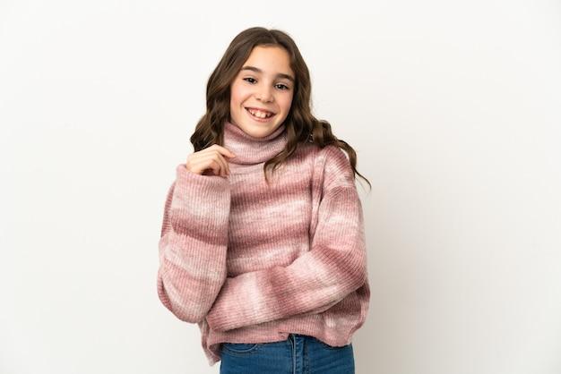 Petite fille caucasienne isolée sur mur blanc en riant
