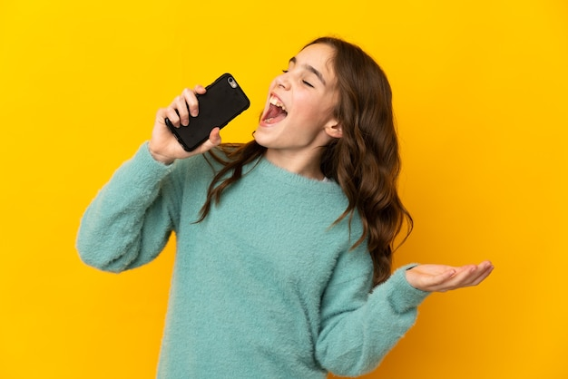 Petite fille caucasienne isolée sur mur jaune à l'aide de téléphone portable et de chant