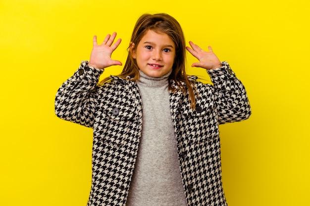 Petite fille caucasienne isolée sur un mur jaune criant vers le ciel, levant les yeux, frustrée.