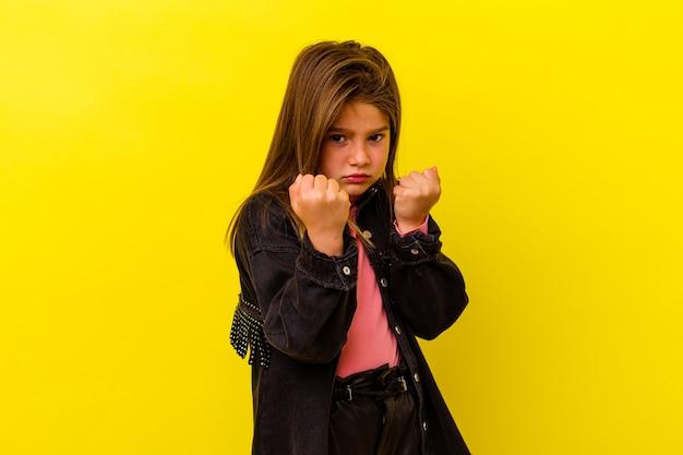 Petite fille caucasienne isolée sur mur jaune montrant le poing à la caméra, expression faciale agressive.