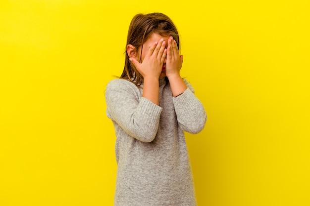 Petite fille caucasienne isolée sur mur jaune peur couvrant les yeux avec les mains.