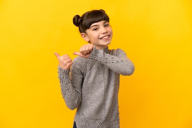 Petite fille caucasienne isolée sur un mur jaune pointant vers le côté pour présenter un produit