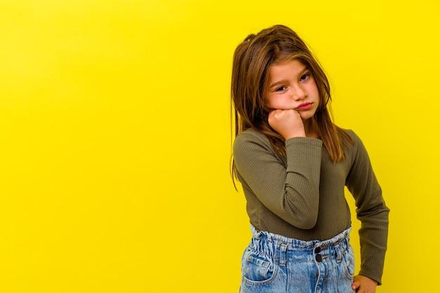 Petite fille caucasienne isolée sur un mur jaune qui se sent triste et pensif, regardant l'espace de copie.