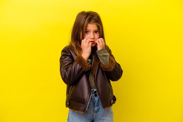 Petite fille caucasienne isolée sur mur jaune se mordant les ongles, nerveuse et très anxieuse.