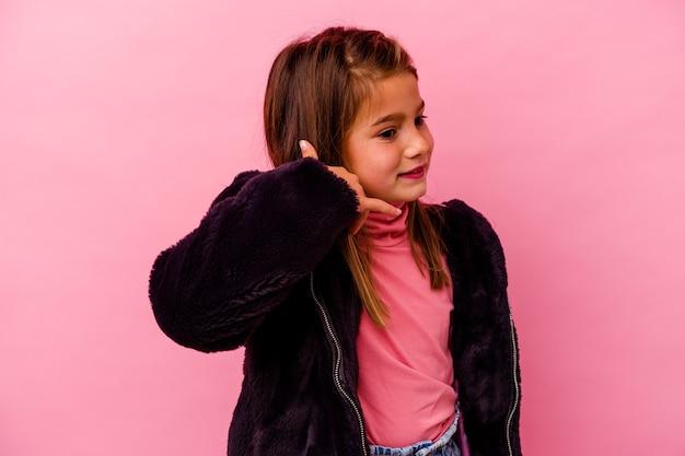 Petite fille caucasienne isolée sur un mur rose montrant un geste d'appel de téléphone mobile avec les doigts.
