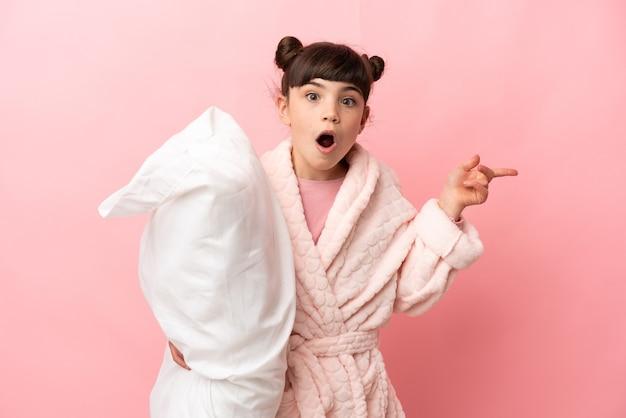 Petite fille caucasienne isolée sur un mur rose en pyjama et surprise en pointant le côté