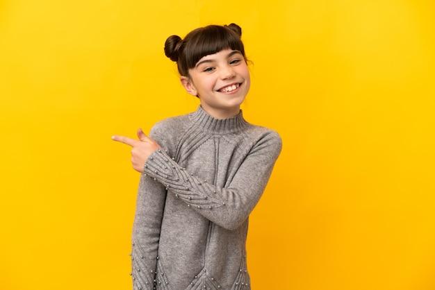 Petite fille caucasienne isolée pointant vers le côté pour présenter un produit