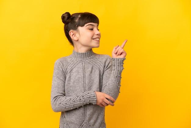 Petite fille caucasienne isolée pointant vers le haut une excellente idée
