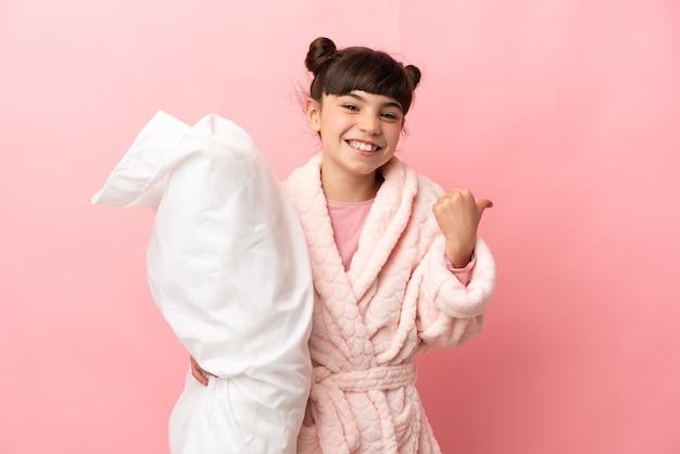 Petite fille caucasienne isolée en pyjama et pointant vers le côté