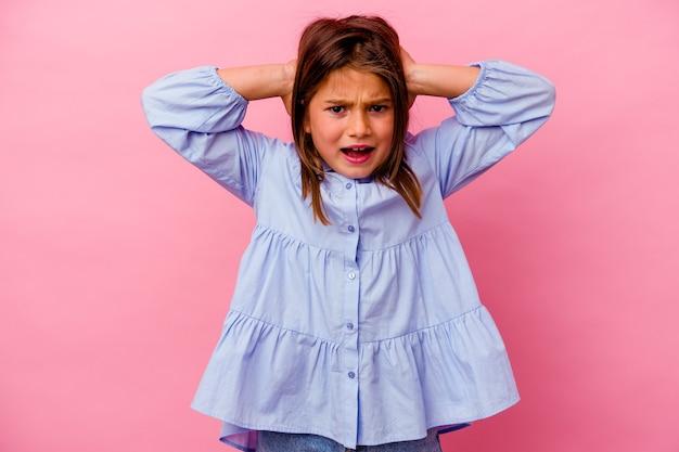 Petite fille caucasienne isolée sur rose couvrant les oreilles avec les mains en essayant de ne pas entendre un son trop fort.