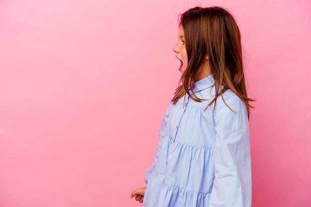 Petite fille caucasienne isolée sur rose en criant vers un espace de copie