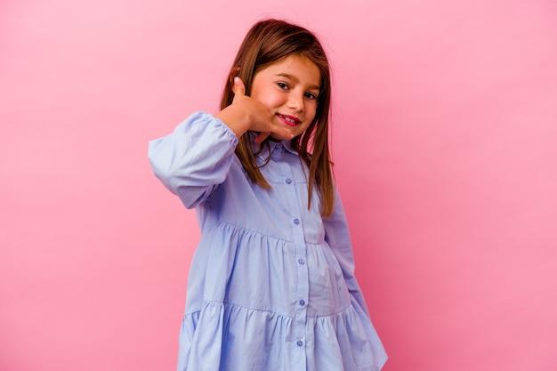 Petite fille caucasienne isolée sur rose montrant un geste d'appel de téléphone mobile avec les doigts.