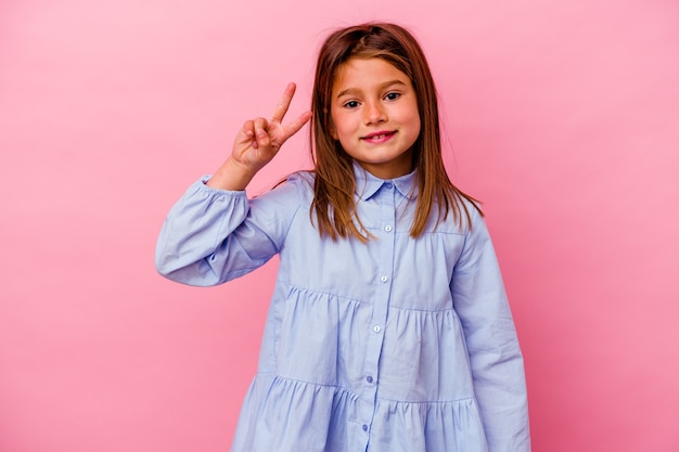 Petite fille caucasienne isolée sur rose montrant le signe de la victoire et souriant largement.