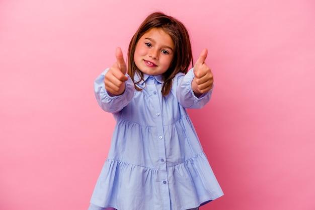 Petite fille caucasienne isolée sur rose avec des pouces vers le haut, applaudit quelque chose, concept de soutien et de respect.