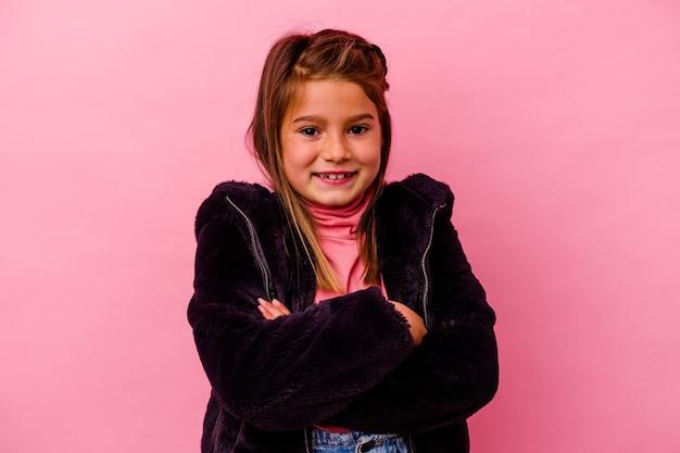 Petite fille caucasienne isolée sur rose en riant et en s'amusant.
