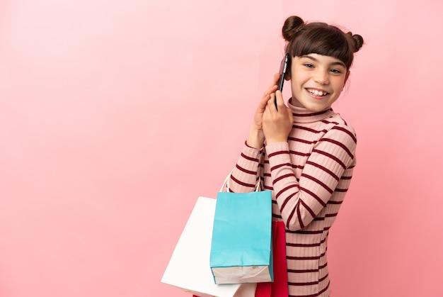 Petite fille caucasienne isolée sur rose tenant des sacs à provisions et appeler un ami avec son téléphone portable