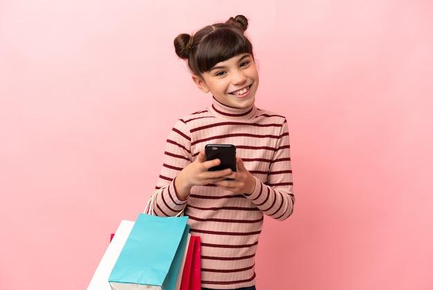 Petite fille caucasienne isolée sur rose tenant des sacs à provisions et écrire un message avec son téléphone portable à un ami