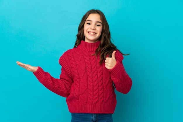 Petite fille caucasienne isolée sur une surface bleue tenant un espace de copie imaginaire sur la paume pour insérer une annonce et avec le pouce levé