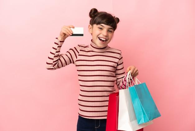 Petite fille caucasienne isolée tenant des sacs à provisions et une carte de crédit