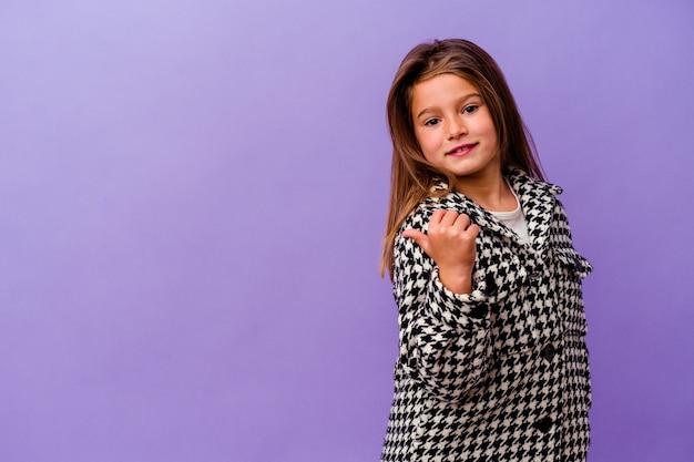 Petite fille caucasienne isolée sur violet petite fille caucasienne isolée sur des points violets avec le pouce à l'écart, riant et insouciant.