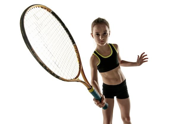 Petite fille caucasienne jouant au tennis sur fond blanc