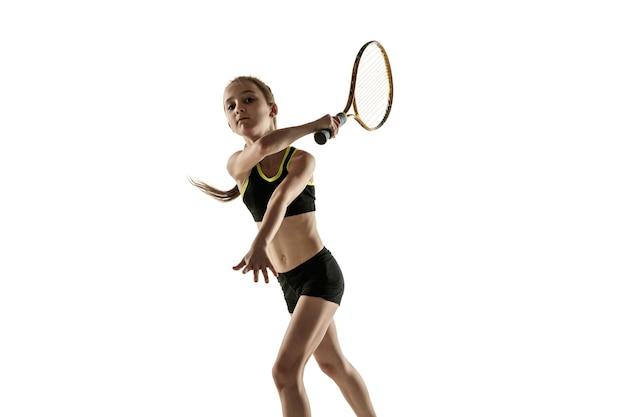 Petite fille caucasienne jouant au tennis isolé sur mur blanc
