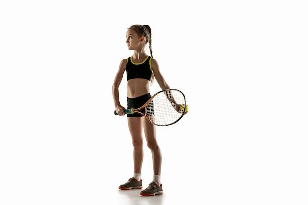 Petite fille caucasienne jouant au tennis isolé