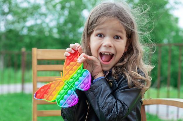 Petite fille caucasienne jouant avec un jouet pop it en silicone arc-en-ciel à la mode
