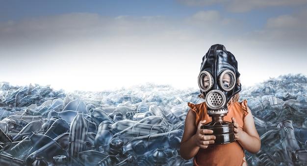 Petite fille caucasienne avec masque à gaz et montagnes de bouteilles en plastique vides derrière elle.