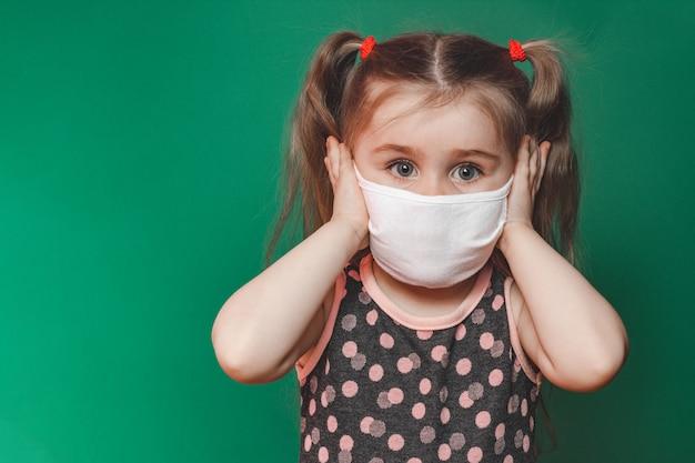 Petite fille caucasienne en masque médical porte une robe à pois rouge en studio sur fond vert et tient sa tête dans la douleur 2020