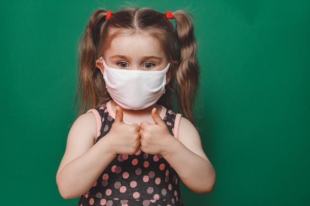 Petite fille caucasienne en masque médical et robe à pois montrant le signe du pouce sur fond vert pendant la pandémie de quarantaine et de coronavirus 2020