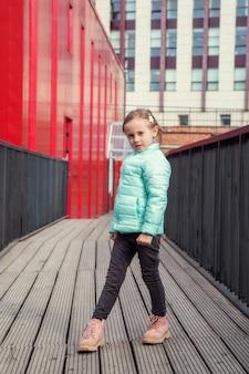 Petite fille caucasienne mignonne posant sur un pont en bois entre les bâtiments colorés modernes regardant la caméra
