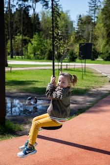 Une petite fille caucasienne monte une balançoire à l'élastique sur le terrain de jeu par une journée ensoleillée